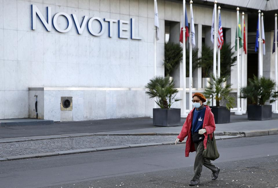 A woman wearing a Covid mask walks past Accor's Novotel Eiffel tower hotel Paris France