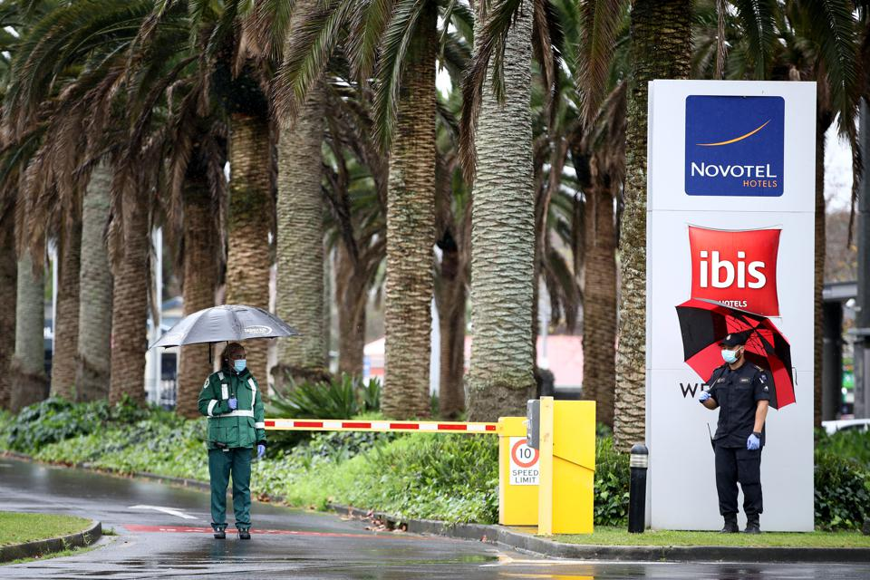 Military staff stand outside a Novotel bis hotel in New Zealand used for Covid quarantine