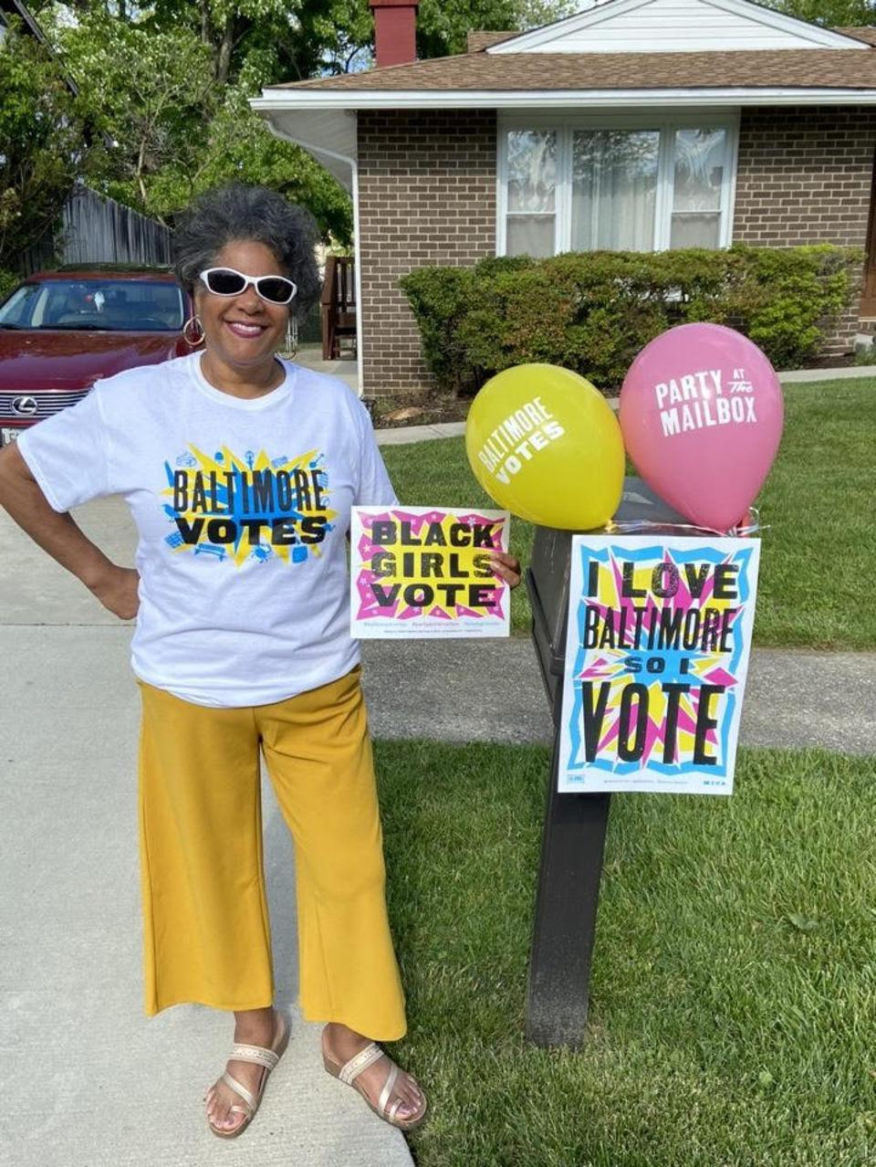 Sharon Eaton standing beside her mailbox with signs and balloons from her party box.