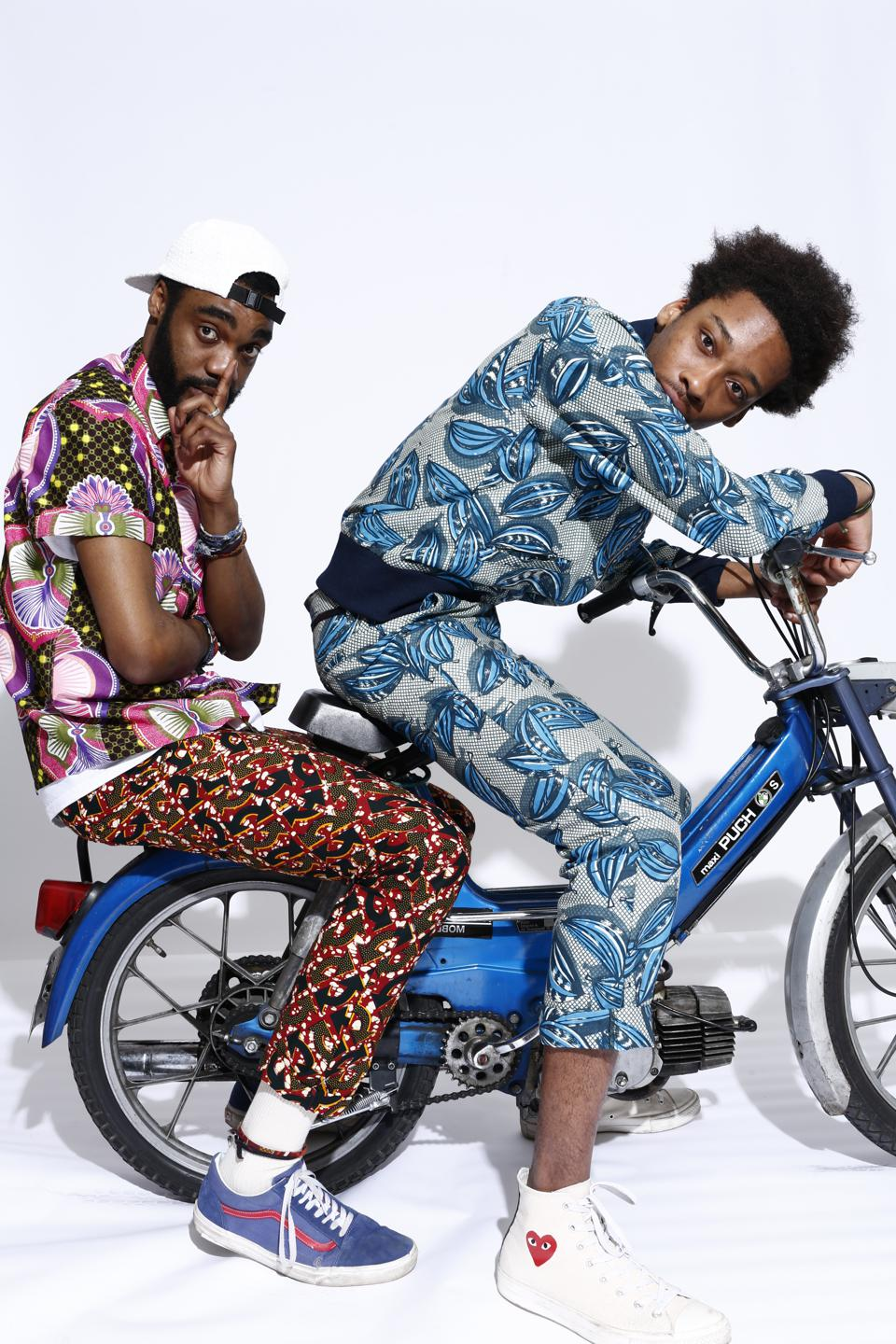 Murphy (wearing hat) wears a shirt model RENÉ in Java African fabric The Chino pant named JOSEPH : all made with old cotton wax fabric  Keziah (right) wears a bomber jacket called MAURICE and Joseph pant. All in cotton wax fabric.