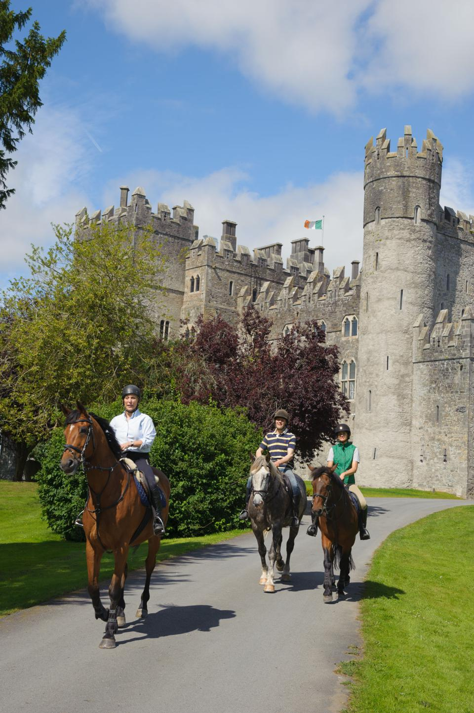 Three people on horseback on a path with  the stone walls and turrets of Kilkea Castle in the background