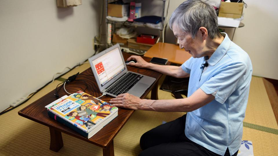 Elderly woman coding on a computer