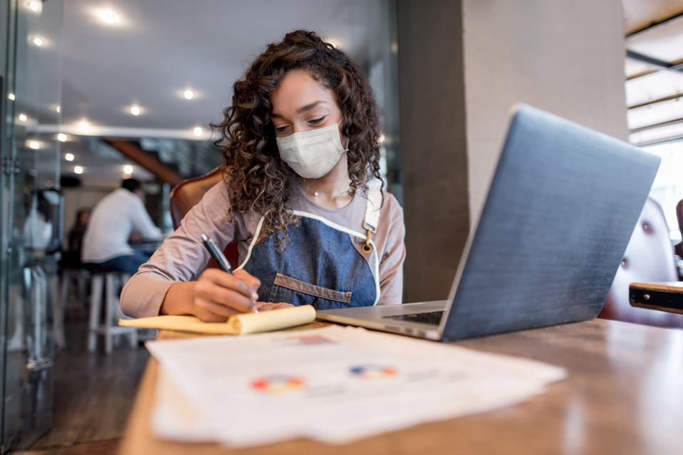 Business manager doing the books at a restaurant wearing a facemask