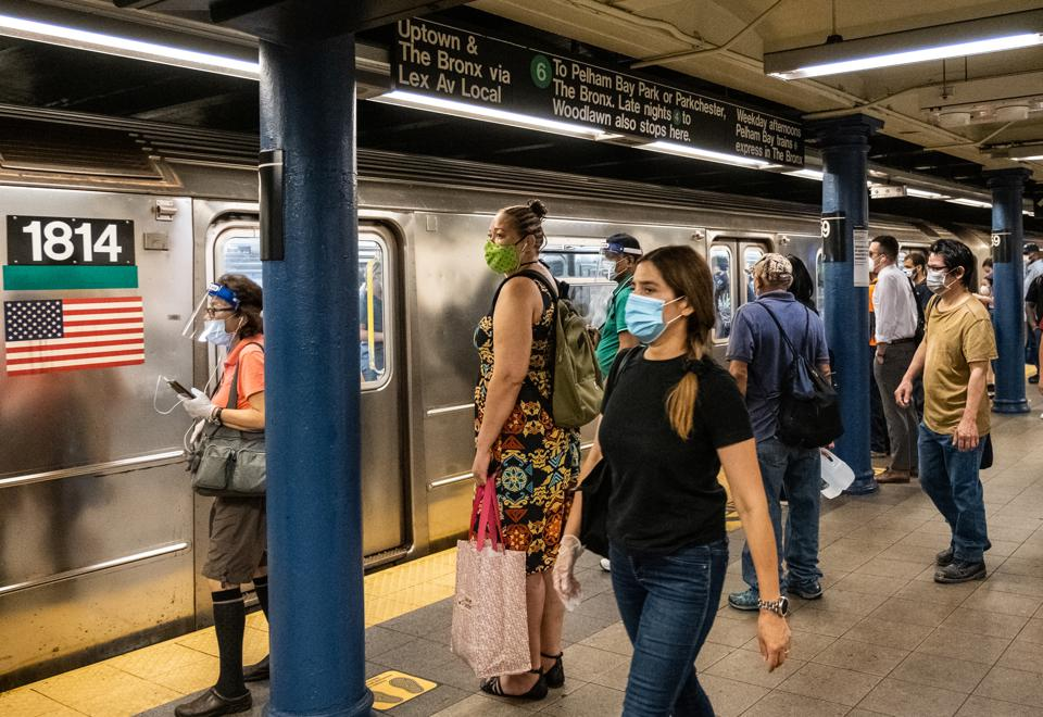 Commuters wearing protective masks wait to board a New York City subway during morning rush hour.