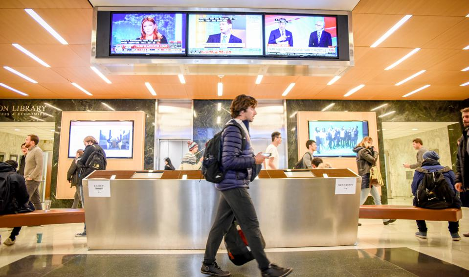 MBA students walking across Uris Hall Lobby in Columbia Business School