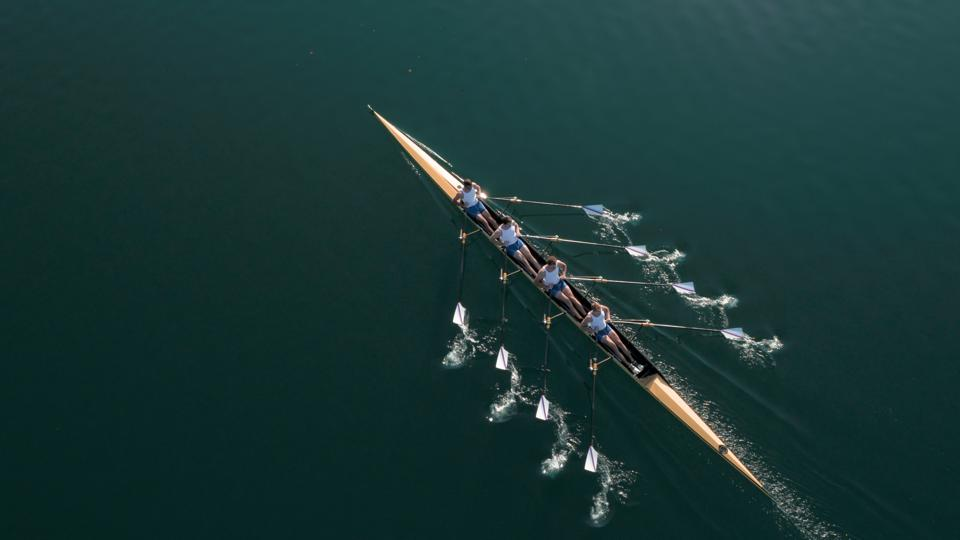 Aerial shot of four rowers in sync. Does not convey probable agony and cursing involved.