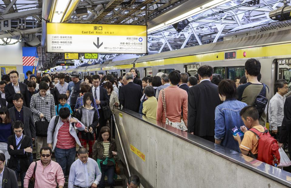 Commuters in Tokyo subway on crowded platform.