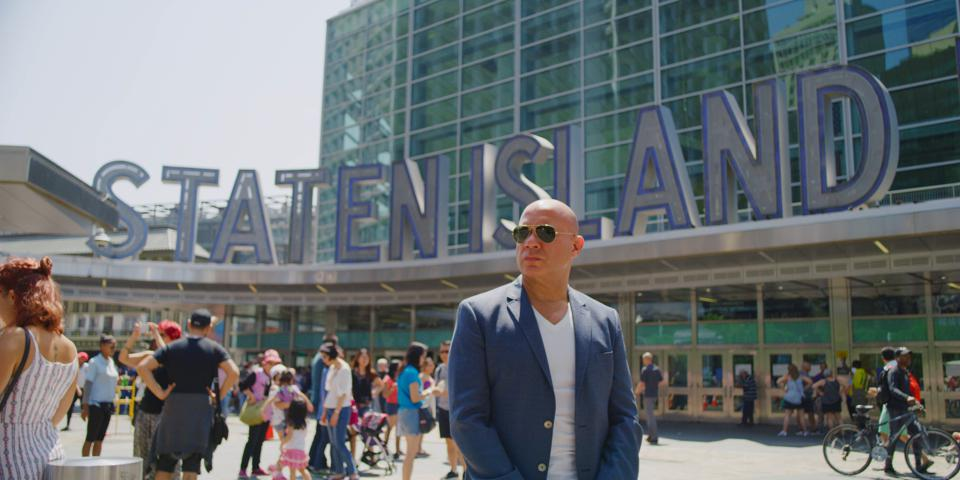 Eric Eremita in front of Staten Island ferry sign