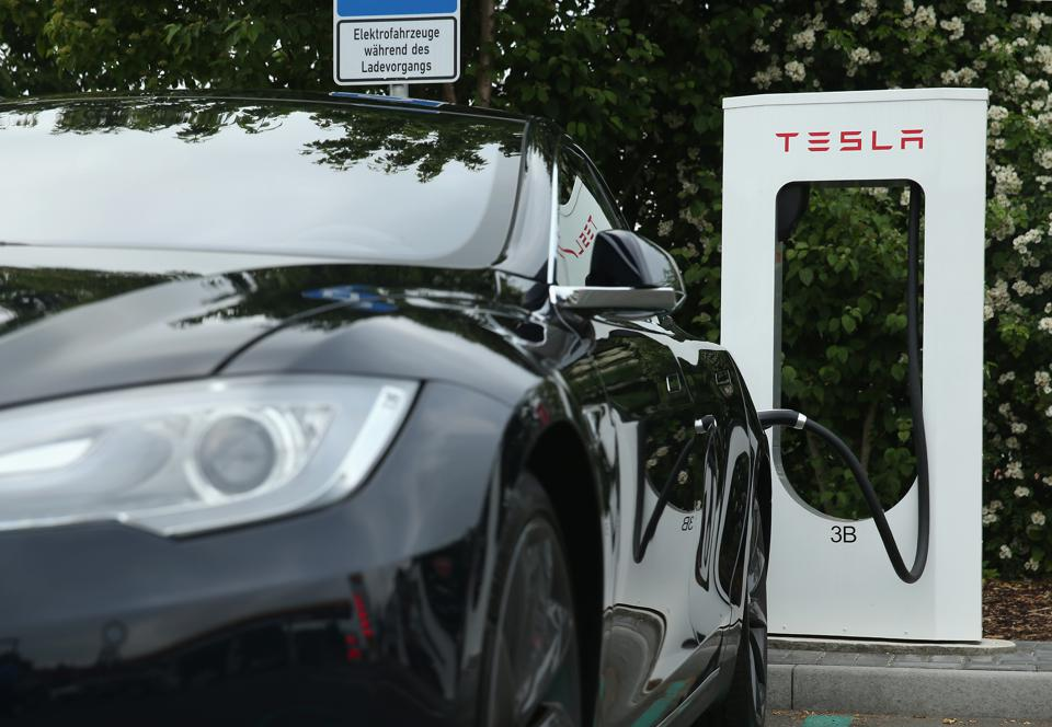 A Tesla being charged. Some consumers are making the switch to an all-electric vehicle.