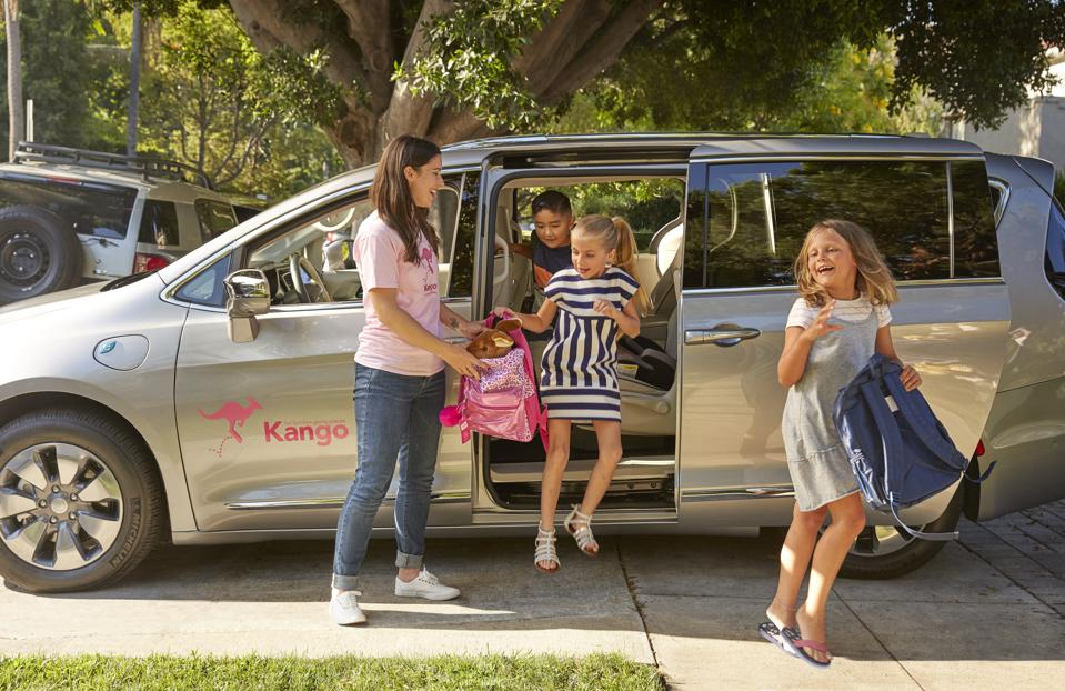 Daughter 1 skipping on the street as she walks from the car; Mother holding backpack for daughter 2 as she gets out of the minivan; son leaning to get out of the minivan quickly following daughter 2
