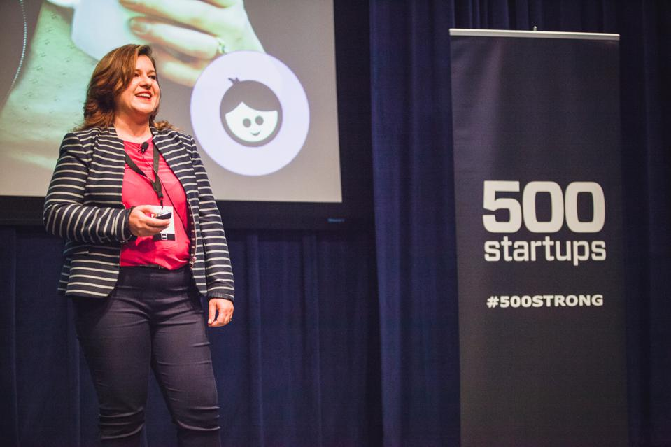 Founder Sara Schaer presenting at 500 startups event on stage in front of PowerPoint screen.