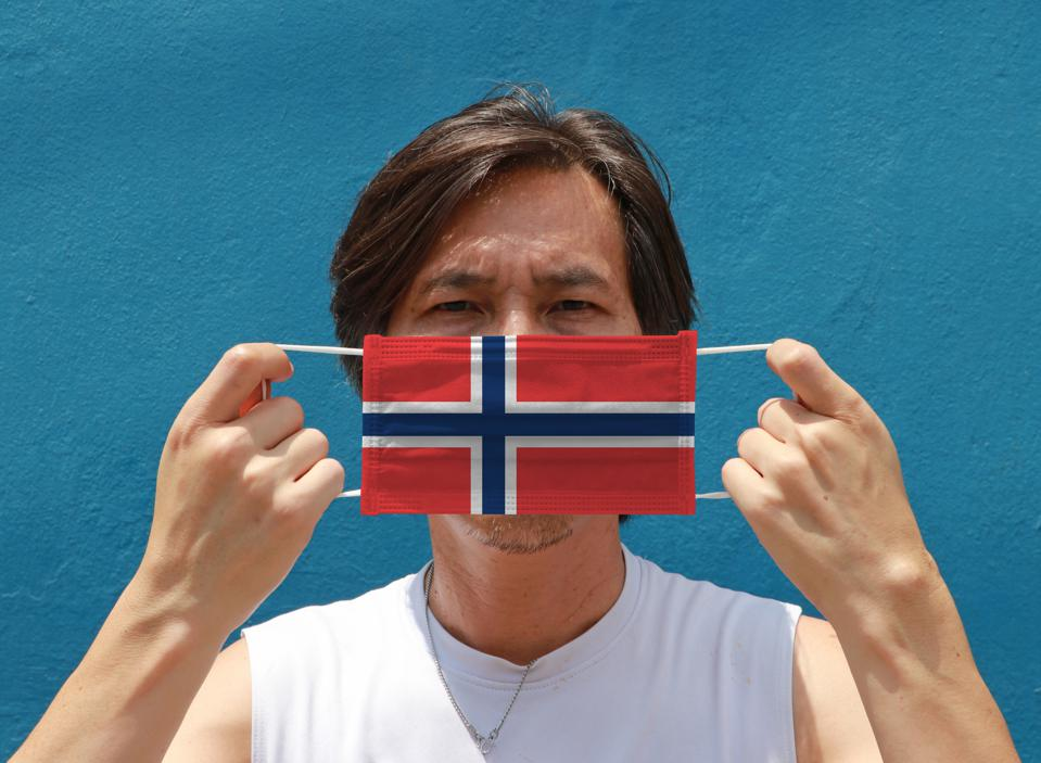 A Norwegian man holding a face mask with the flag of Norway.