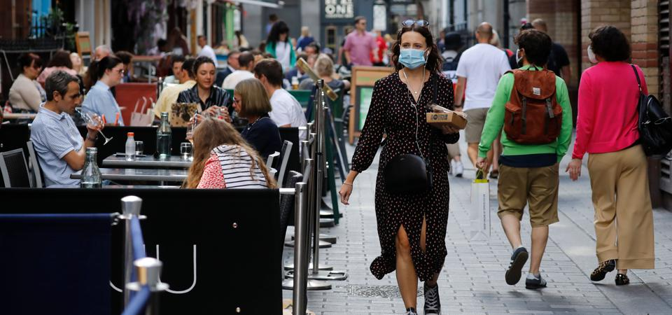 Woman wearing a face mask walks past outdoor diners.
