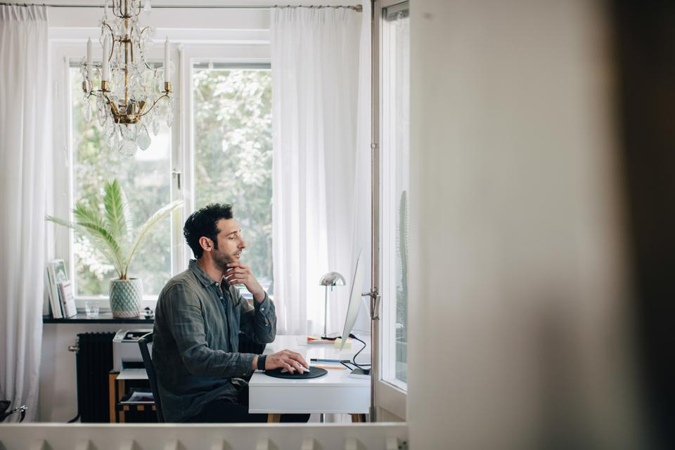 Serious young businessman using computer at desk in home office