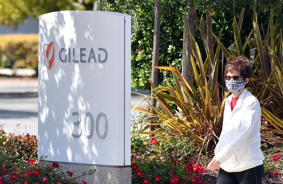 A woman wearing a mask walks by Gilead Sciences headquarters sign in Foster City, California on April 30, 2020.
