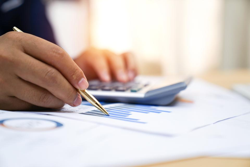 Businessman analyzing investment charts with calculator, Accounting,account,Accounting concept