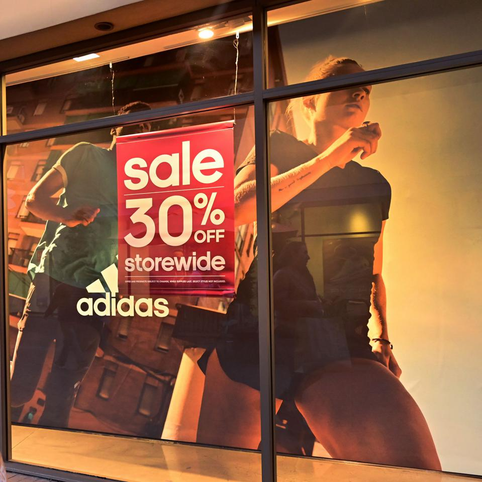 Adidas store front showing a promotional sign of 30 precent off