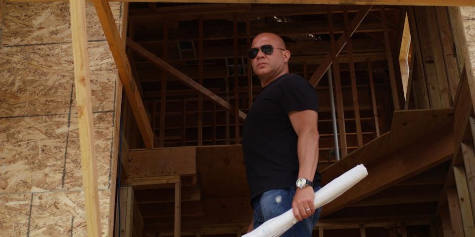 Man in black t-shirt holding blueprints.