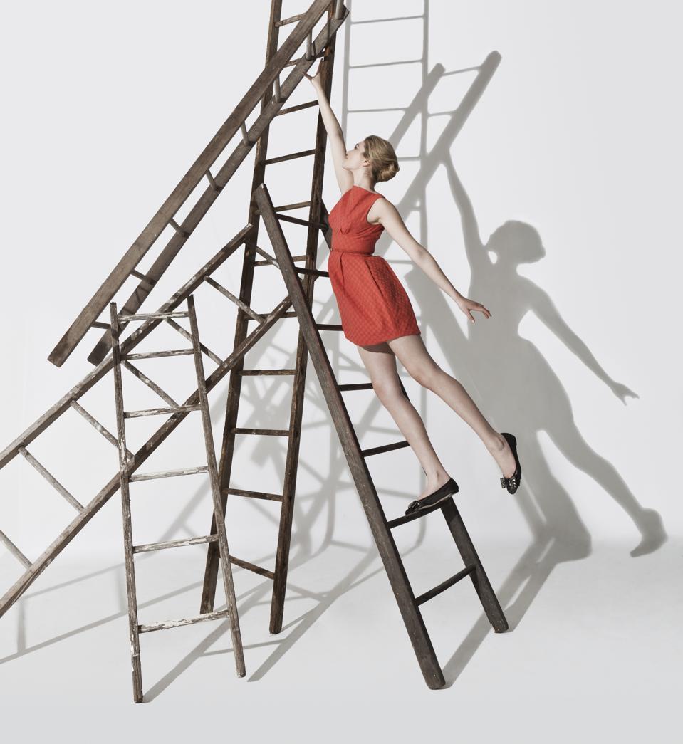 Business woman climbing up ladders construction