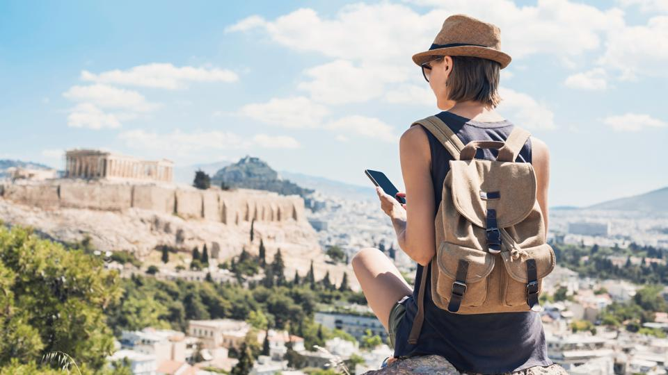 Woman using smart phone on vacations in Athens