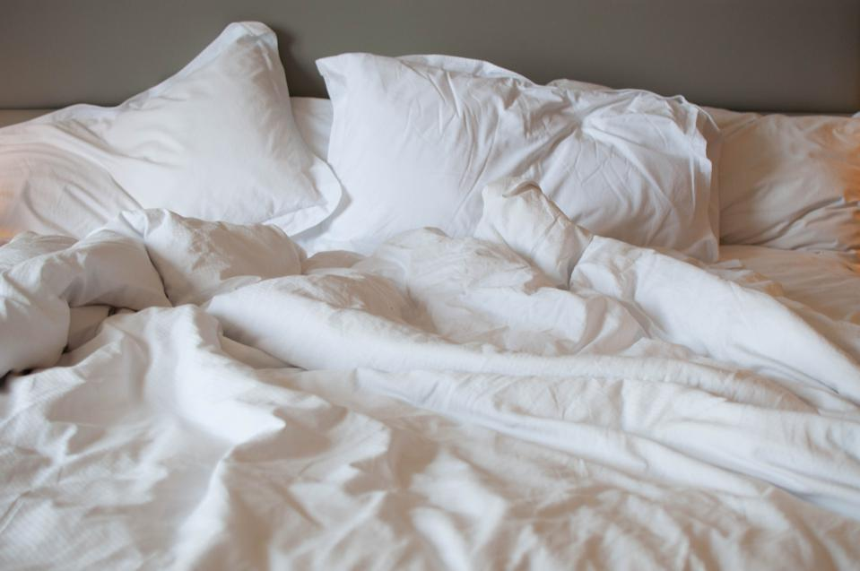 A messy bed with comforter and pillows