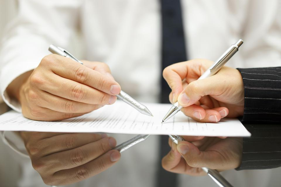 Health Supplements Business man is pointing woman where to sign document