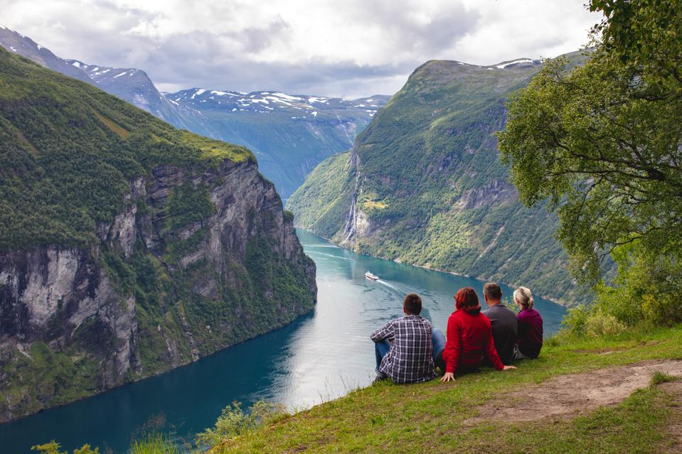 Four people sitting on the ground looking at the Geirangerfjord in Norway.
