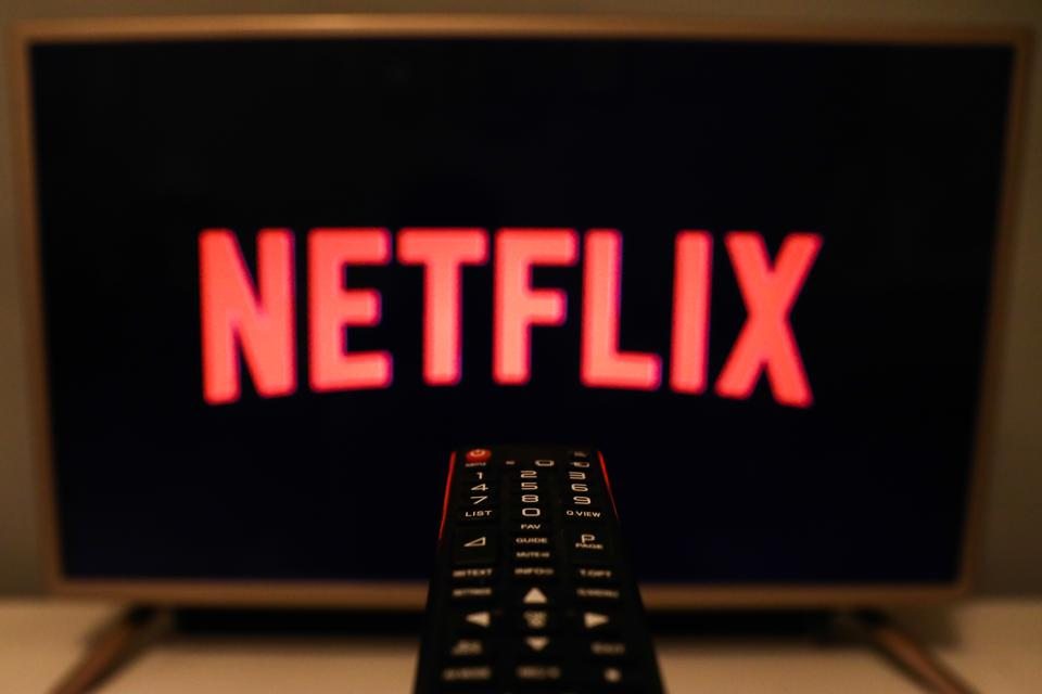 Netrflix logo in red on screen with a TV remote pointing towards it