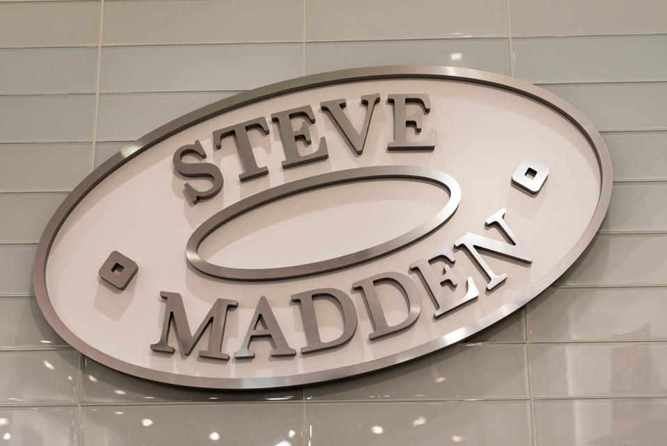 Logo of Steve Madden hanging from a tile wall. Steve Madden...