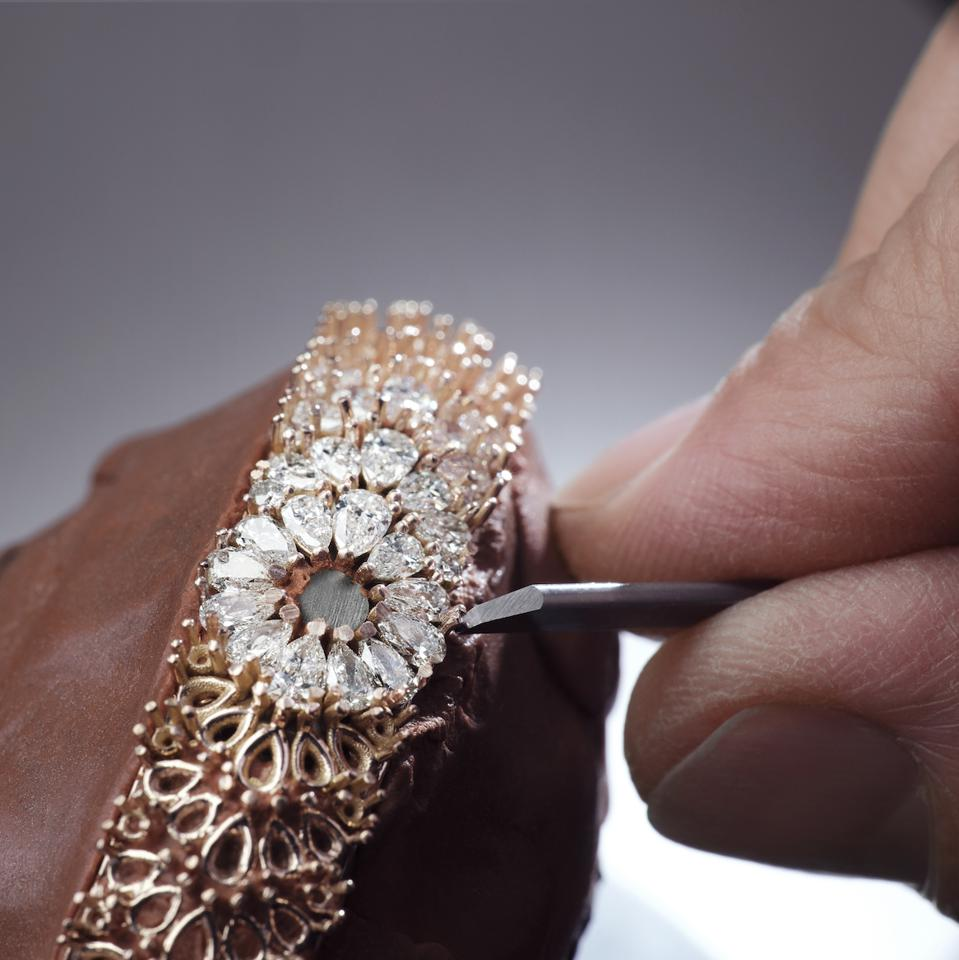 An artisan hand-sets diamonds on the Snowdrop watch