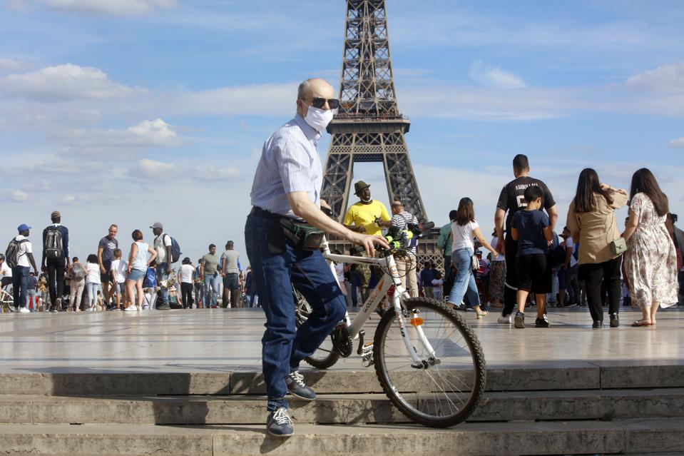 Man with Covid mask and a bike in front of the Eiffel Tower Paris France