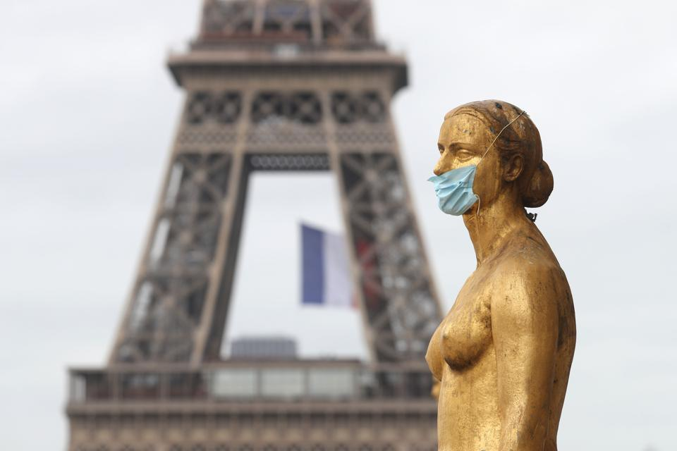 Statue wearing a mask in front of the Eiffel Tower Paris France