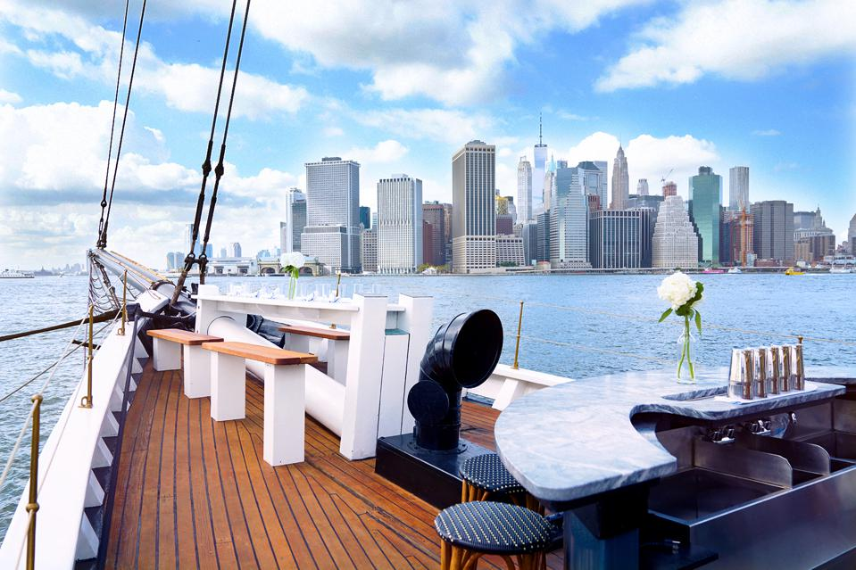 The front of a schooner with the Manhattan skyline across the harbor.
