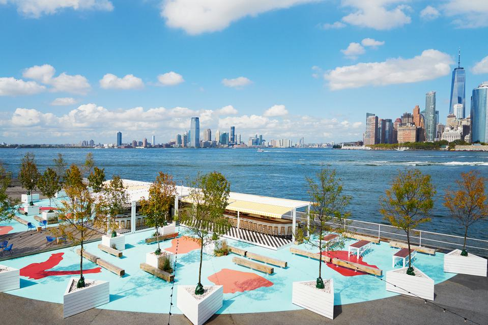 The deck of a restaurant surrounded by the waters of New York harbor and the city's skyline.