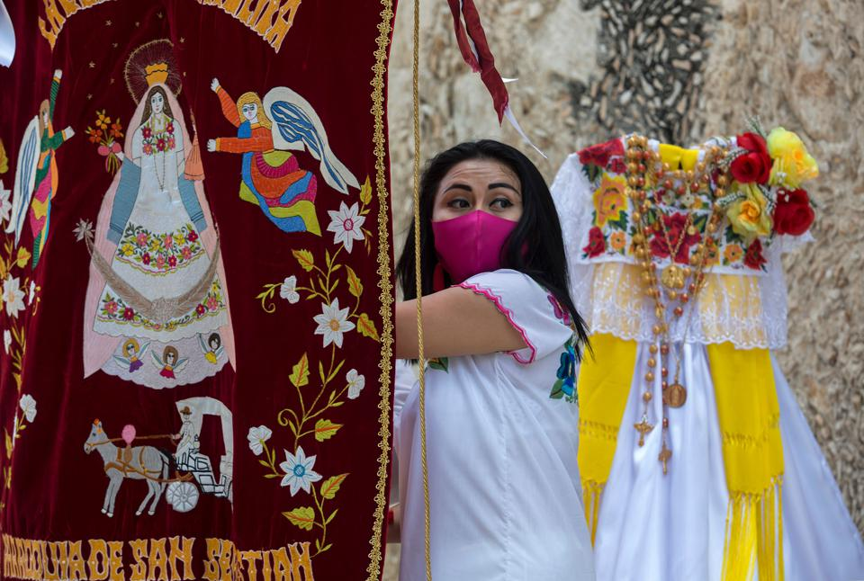 A woman wearing a a Covid face mask with bright costumes in Mexico