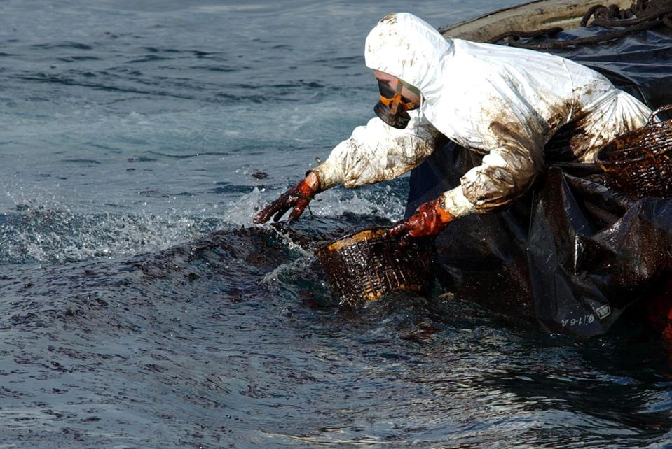 A fisherman from Cangas collects oil fro