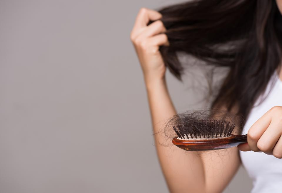Healthy concept. Woman showing her brush with long hair loss and looking at her hair.