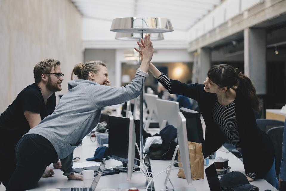 Happy inside sales repsgiving high-five over desk in office