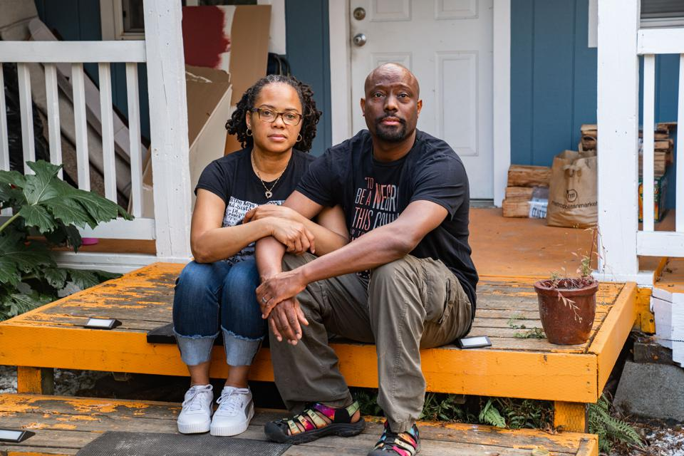 man and woman sit on front porch