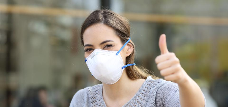 Woman doing thumbs up wearing protective mask