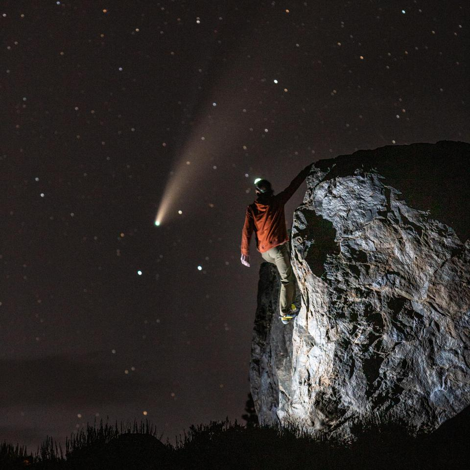 man climbing rock meteor in background