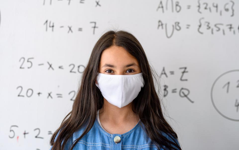Girl with face mask back at school after covid-19 quarantine and lockdown.