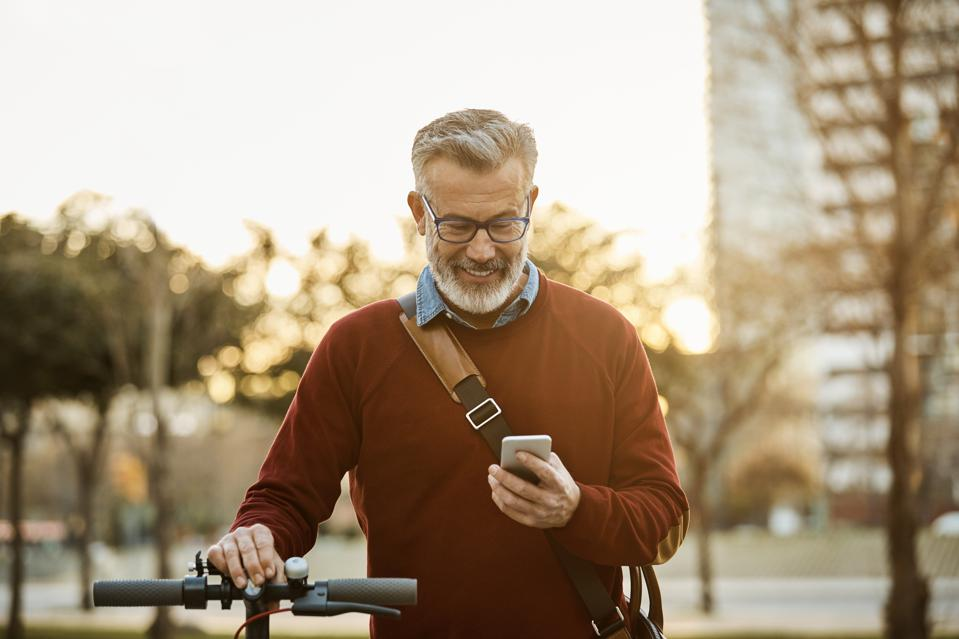 Happy man with mobile phone and bicycle in city