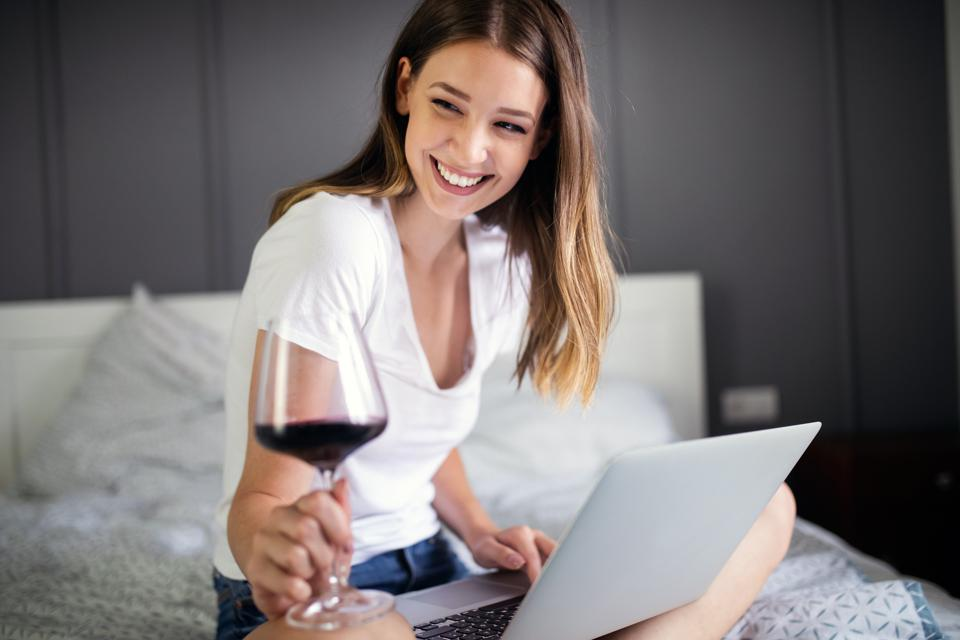 Happy woman using a laptop searching online on the bed at home