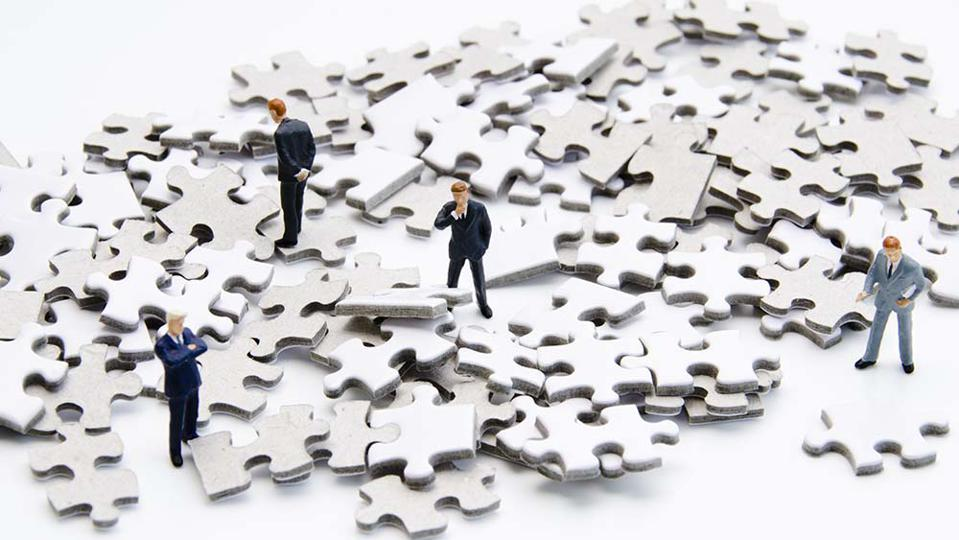 A pile of puzzle pieces with small businessmen figurines examining the pile.