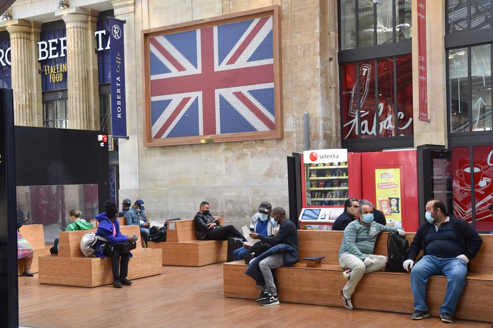 Passengers await their train next to United Kingdom flag at Gare du Nord train station in Paris.