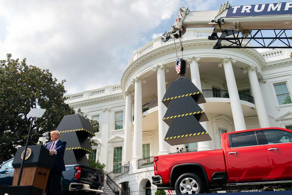 Image from the south lawn of the White House with President Trump at a podium in front of two trucks with weights in the back, one with the weights lifted out to depict the administration's reduction in the number of federal regulations.