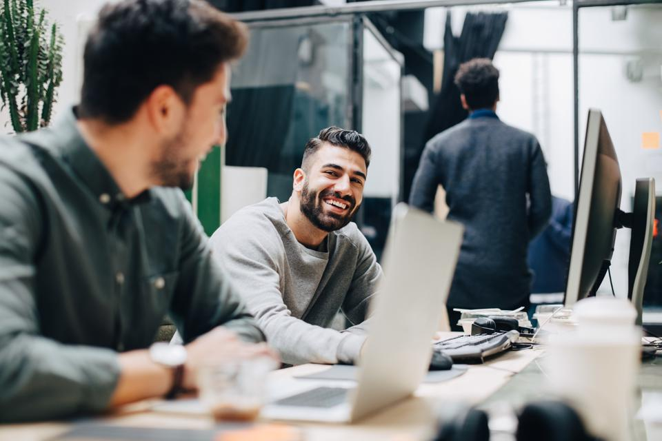 Smiling male colleagues looking at each other while sitting by desk in office