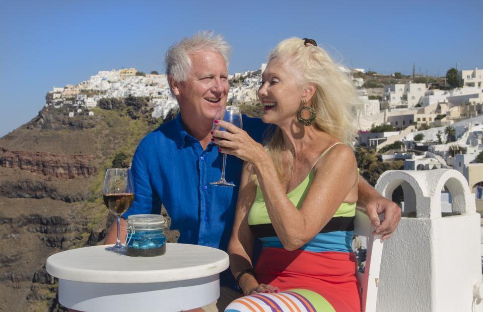 Santorini Greece Retired Couple On Holiday Having Fun Having Wine On Cliff In Fira