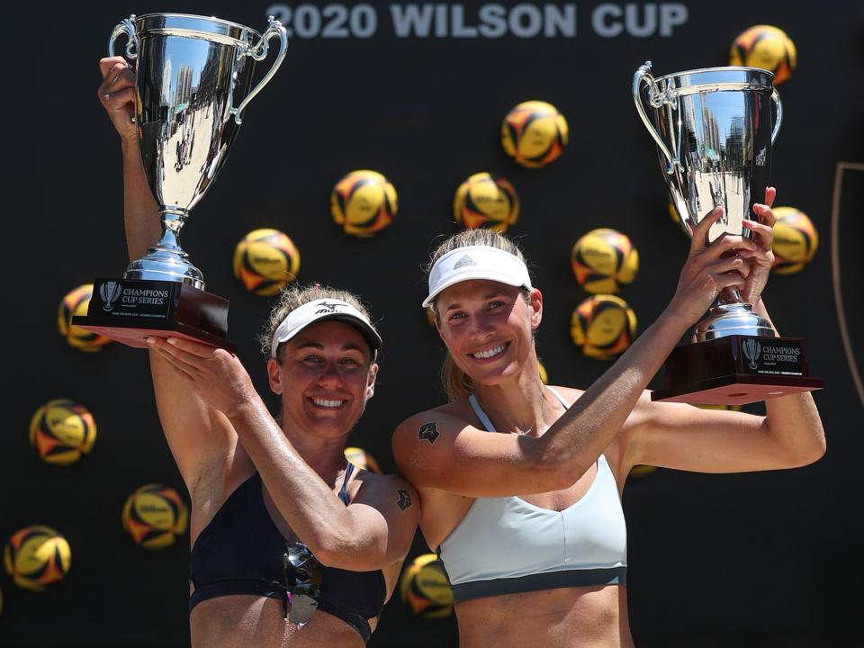 April Ross (l.) and Alix Klineman (r.) host their championship trophies from the 2020 AVP Wilson Cup.